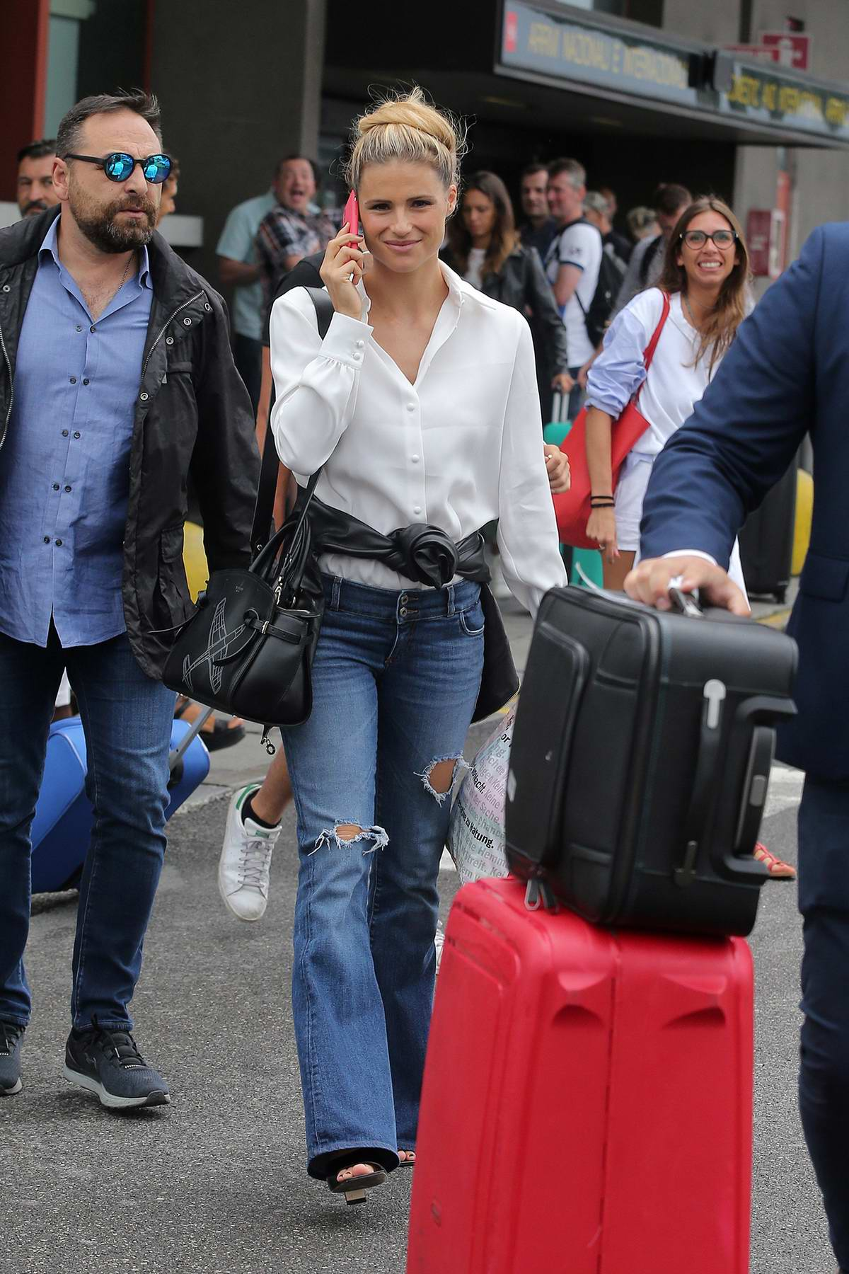 Michelle Hunziker spotted in a white shirt and ripped jeans as she arrives at the airport in Milan, Italy