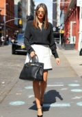 Miranda Kerr looks perfect in a black shirt and white miniskirt with black tote and pumps while heading out in New York City