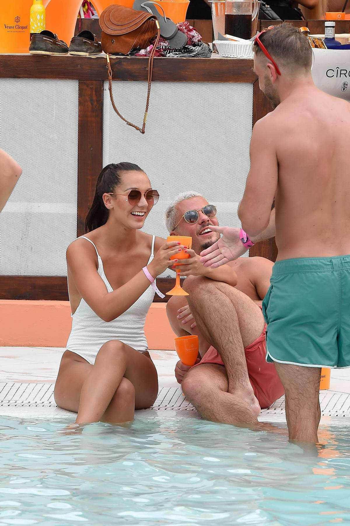Nadine Mulkerrin wears a white swimsuit as she enjoys a pool party with boyfriend Roy Douglas-Speed while on holiday in Spain