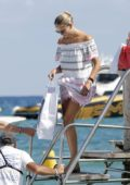 Natasha Poly spotted in a beach dress as she leaves Le Club 55 on a speedboat in Saint Tropez, France