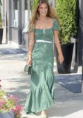 Nina Agdal smiles for the camera while out wearing a green dress in New York City