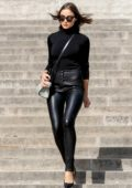 Olivia Culpo sports black top, black leather pants with white snakeskin handbag during a photoshoot at Trocadero Plaza in Paris, France