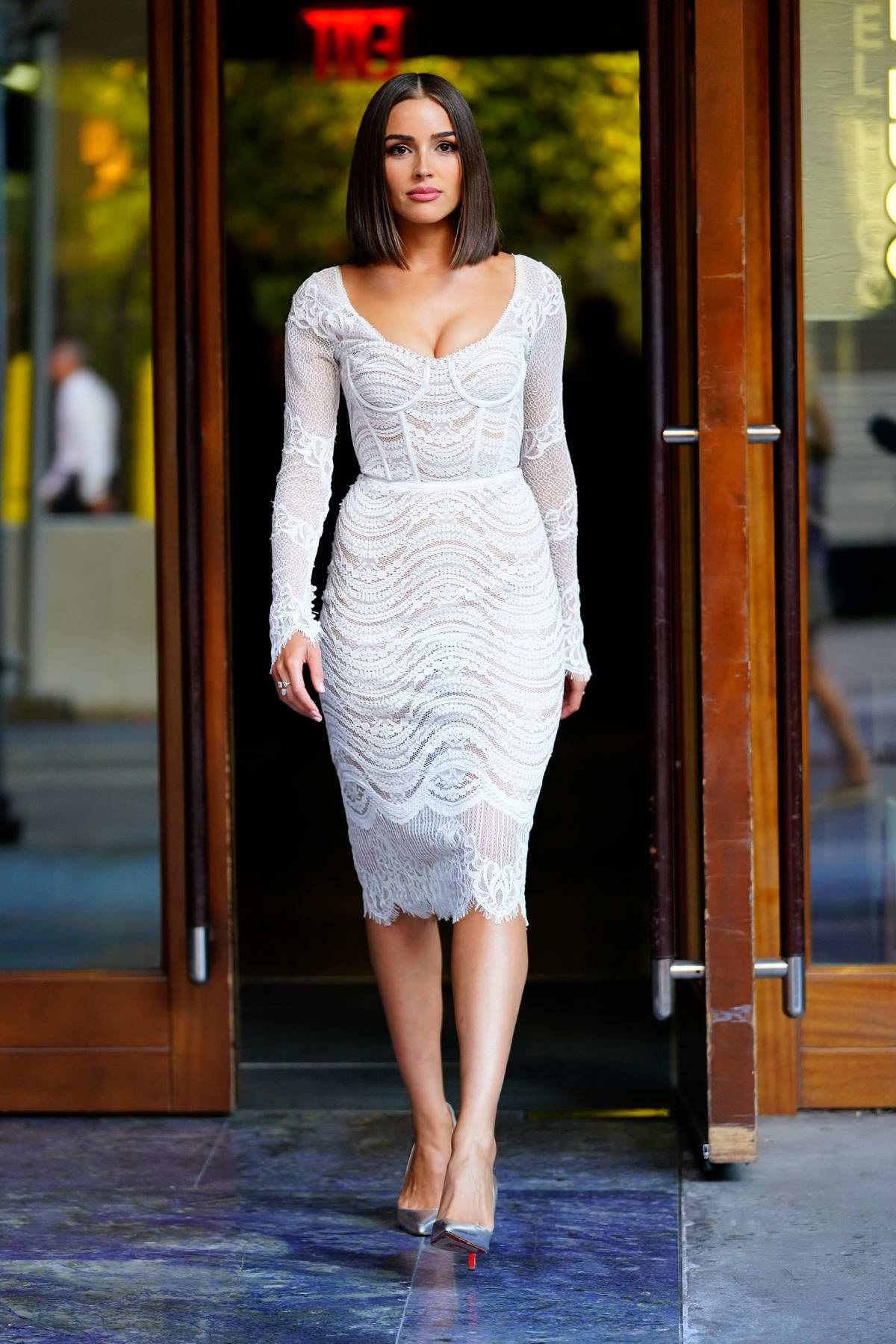 Olivia Culpo wears a formfitting white lace dress as she heads out in New York City