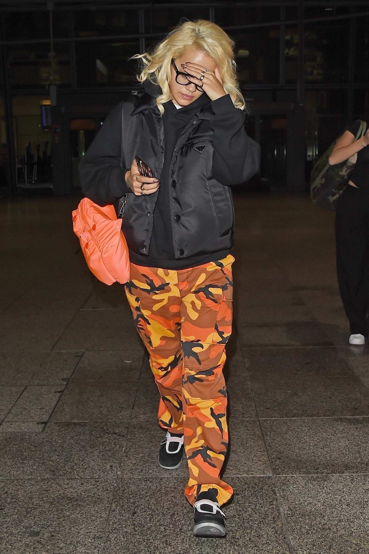 Rita Ora covers her face as she touch down at Heathrow airport wearing orange camo pants and black jacket, London, UK