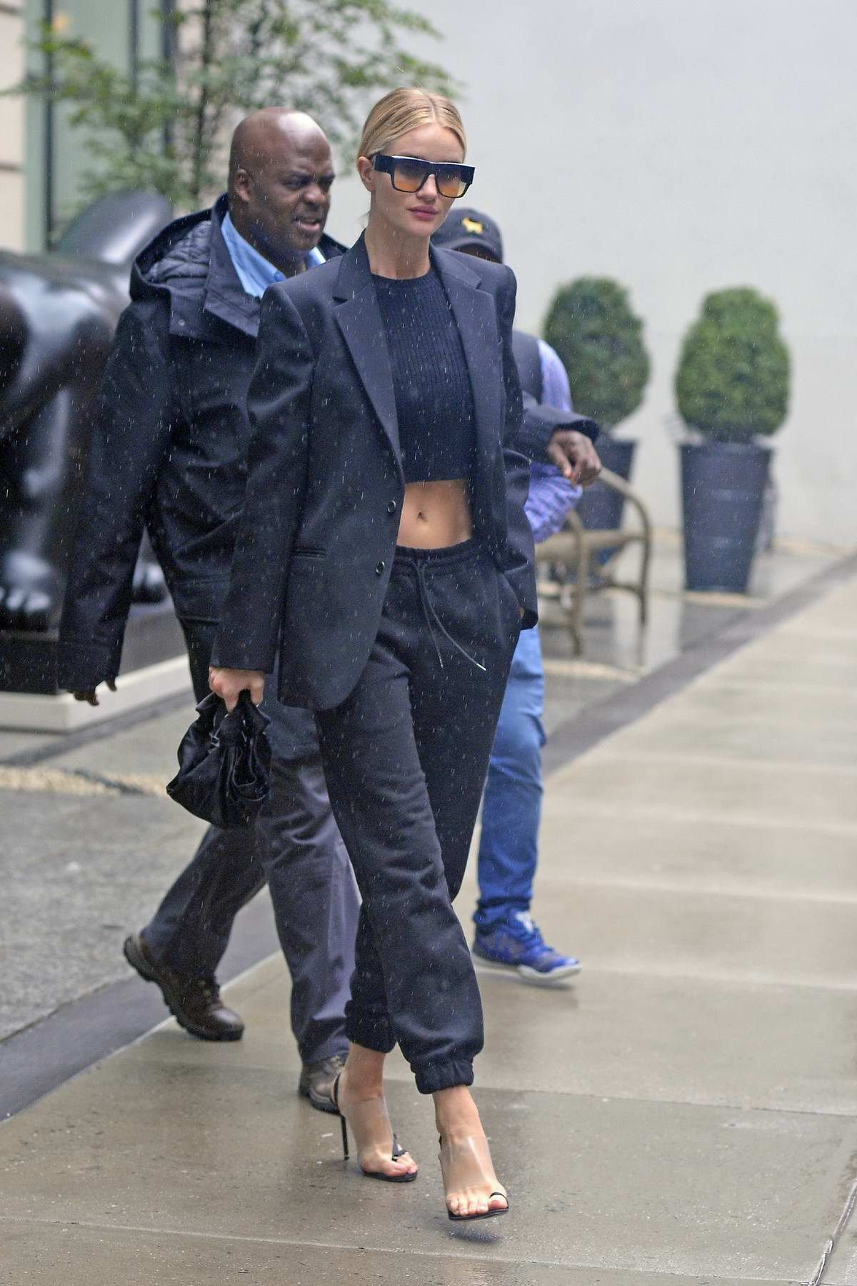 Rosie Huntington-Whiteley seen wearing black pantsuit over black crop top while heading out in rain in New York City