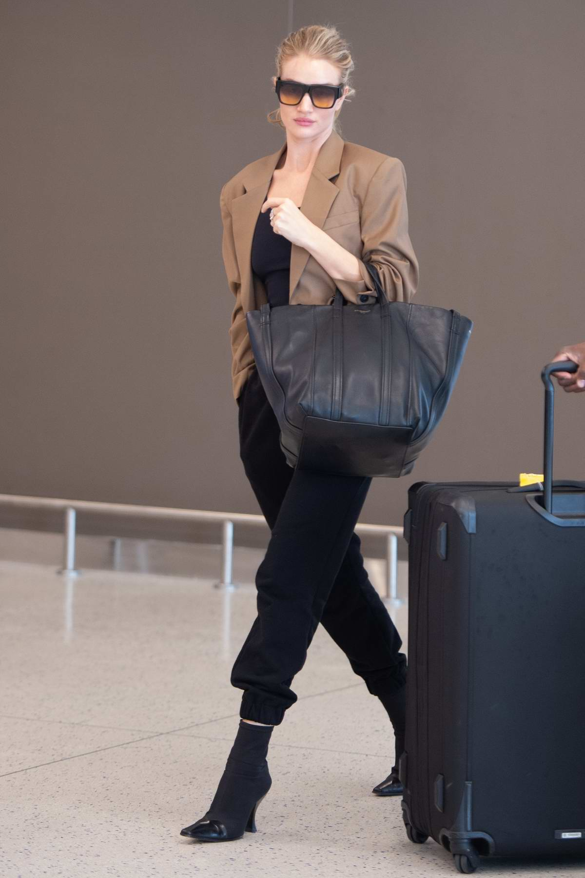 Rosie Huntington-Whiteley wore a brown blazer with black pants and heels as she arrives at JFK airport in New York City