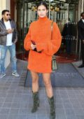 Sara Sampaio wears an orange dress with olive green suede boots as she heads out of Royal Monceau Hotel in Paris, France