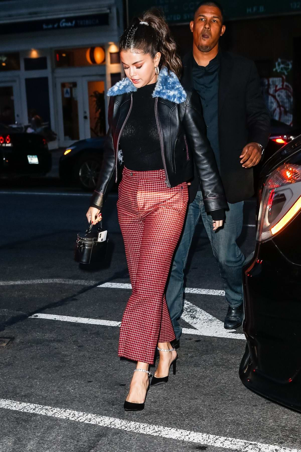 Selena Gomez wears a black leather jacket with red and white checkered pants while out with friends for dinner in New York City