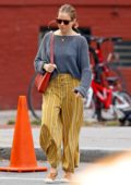 Sienna Miller steps out wearing a grey sweater and yellow striped pants in New York City