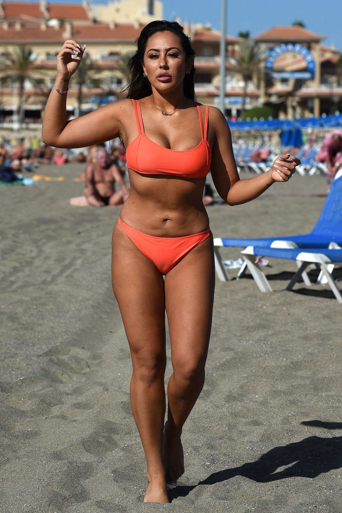 Sophie Kasaei wears an orange bikini while at the beach in Mykonos, Greece