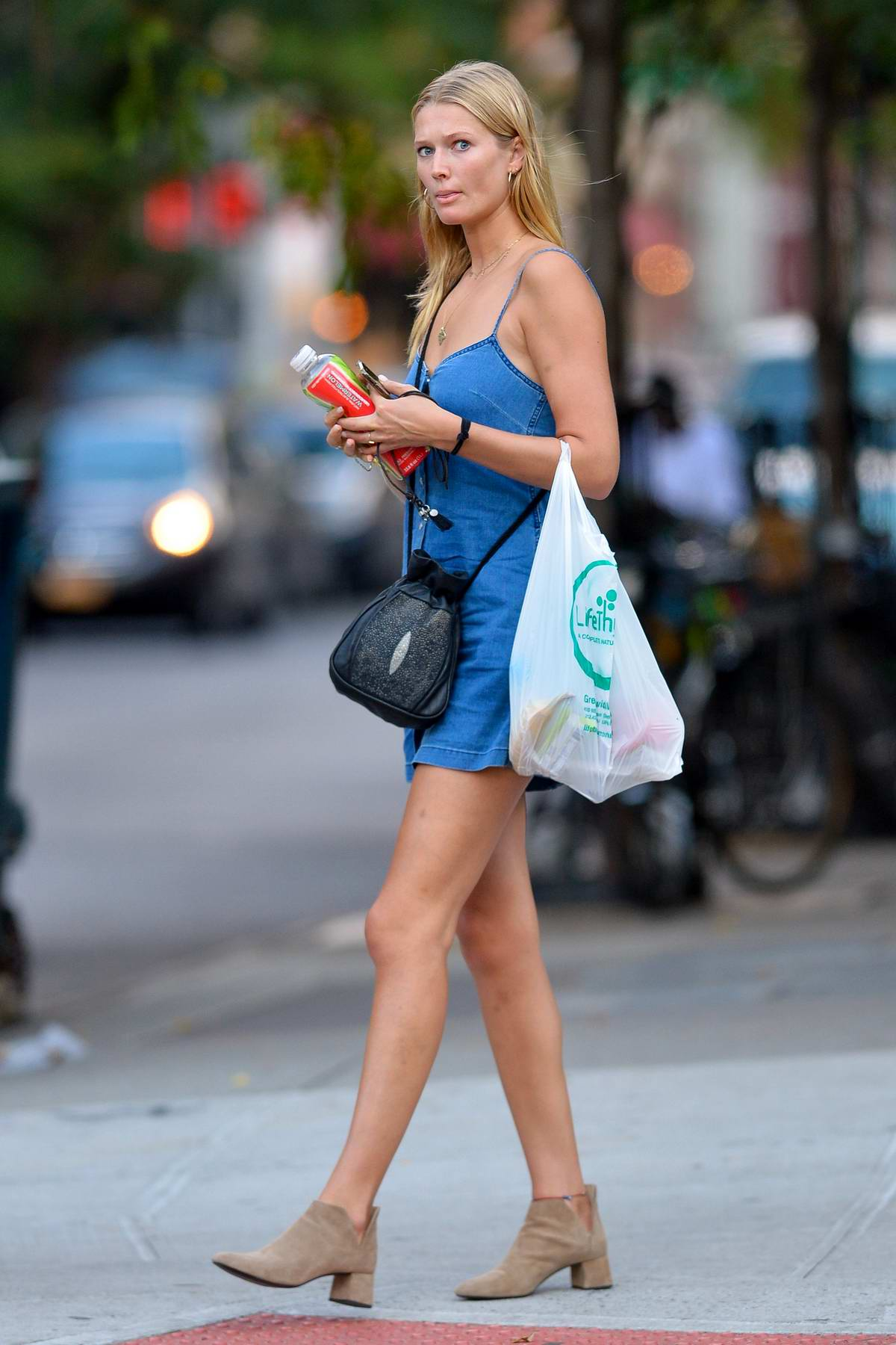Toni Garrn wears a blue denim minidress while out on a stroll in New York City
