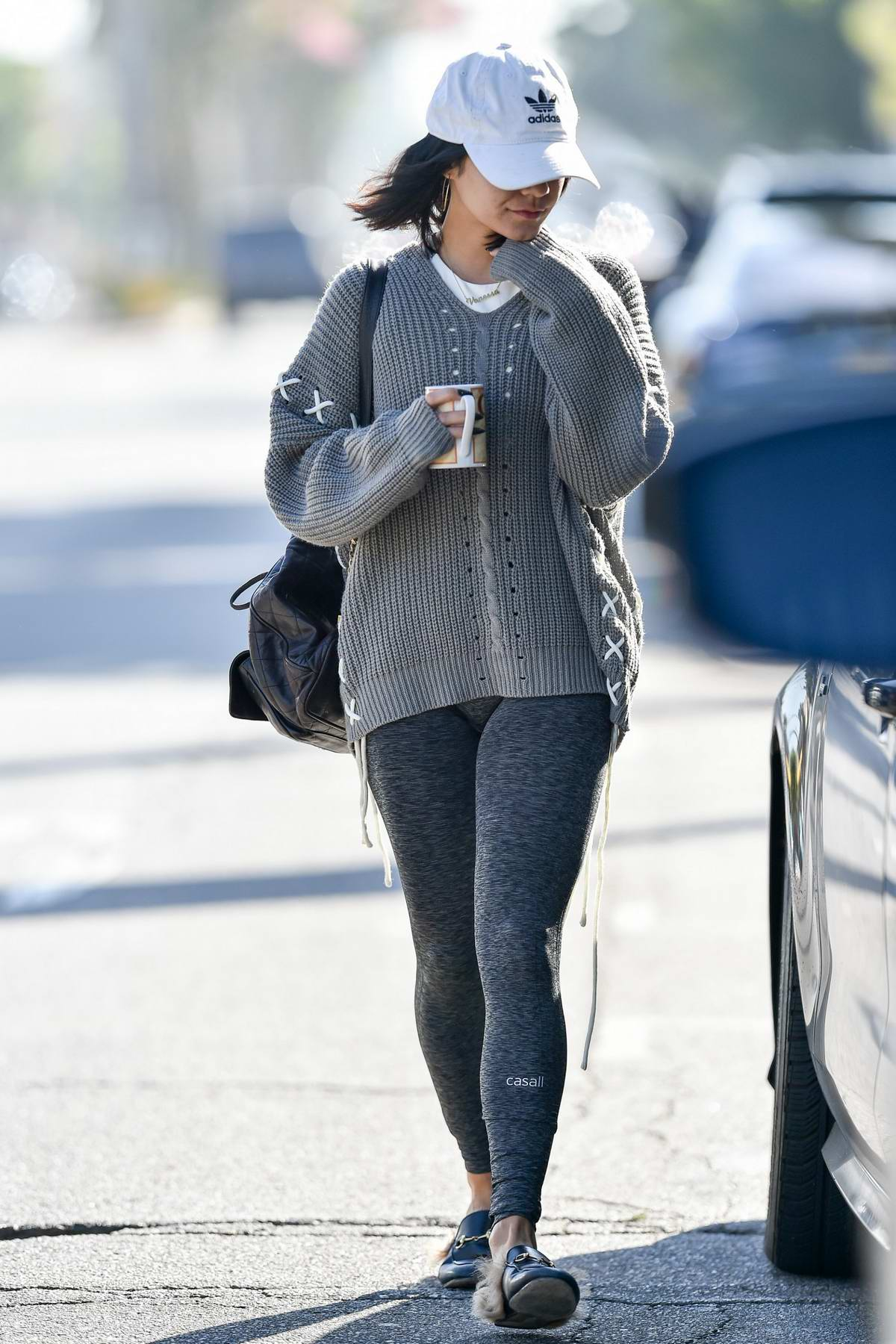 Vanessa Hudgens steps out in a grey sweater, leggings with an Adidas hat as she leaves a Pilates class holding a cup in Los Angeles