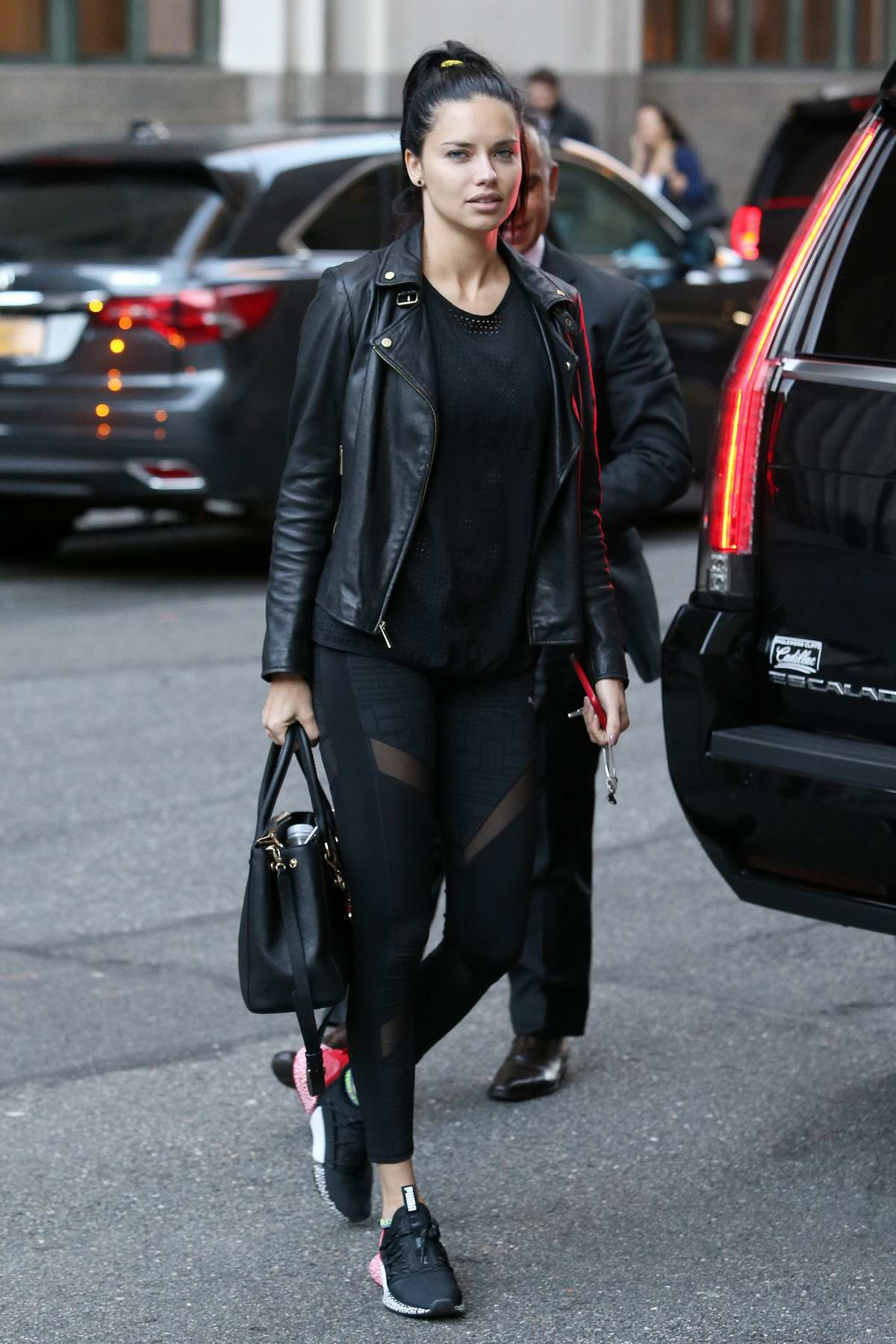 Adriana Lima rocks a black leather jacket to match her Puma gym wear as she arrives back to her hotel after workout , New York City