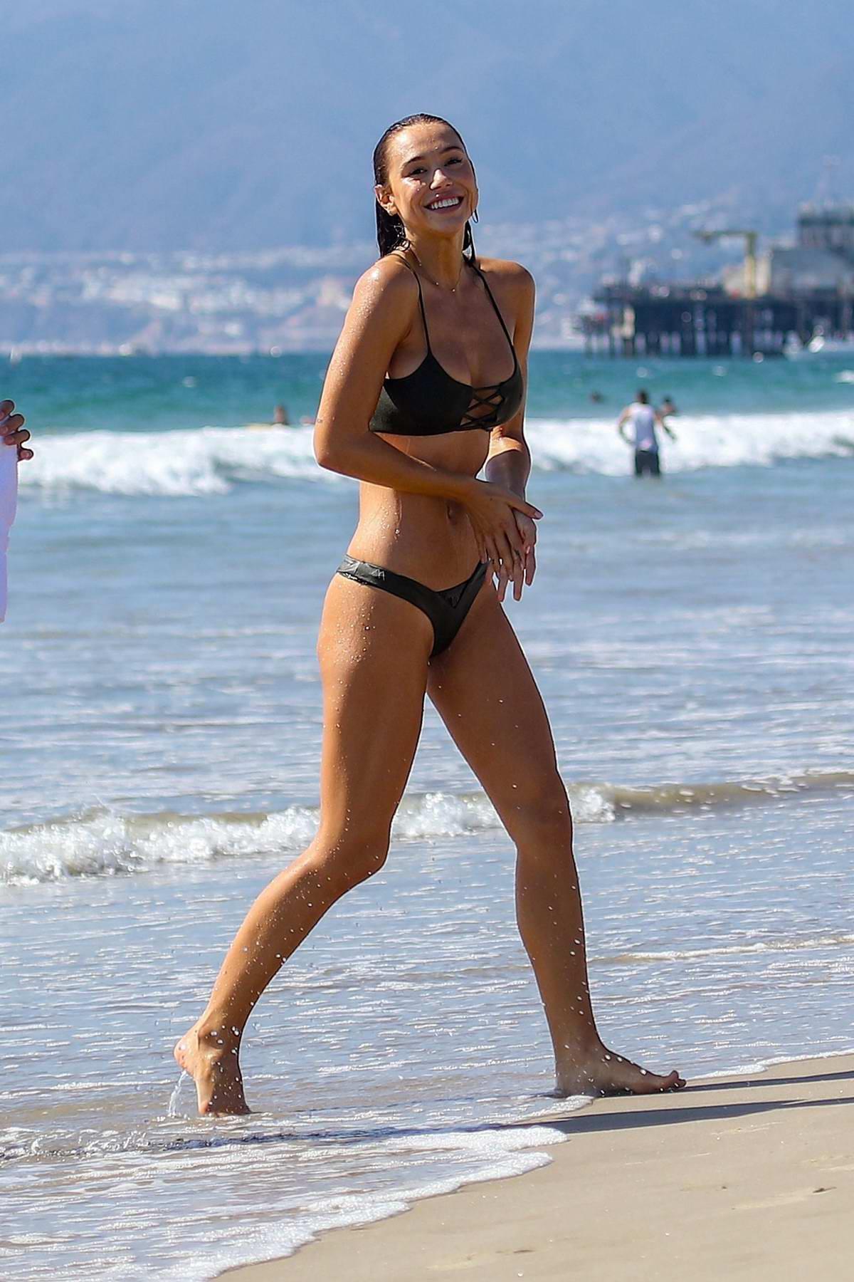 Alexis Ren wears a green bikini while enjoying a beach day in Santa Monica, California