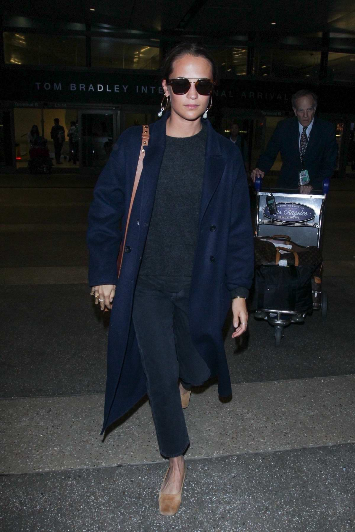 Alicia Vikander spotted in blue trench coat as she touch down at LAX airport in Los Angeles