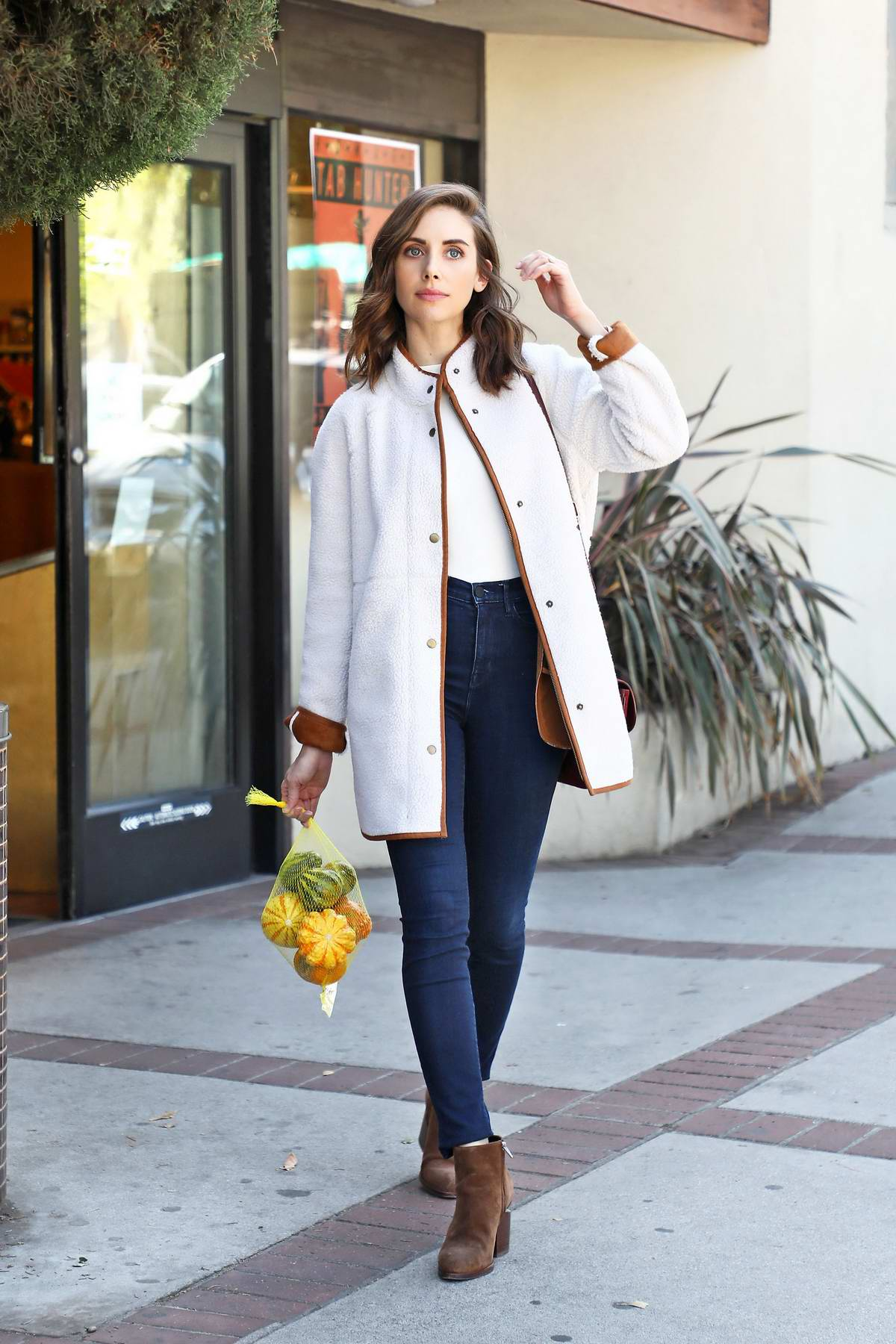 Alison Brie looks lovely in a white sherpa coat and jeans while shopping for some pumpkins at a market in Los Angeles