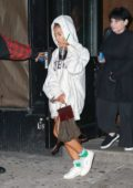 Ariana Grande holds onto her Starbucks as she leaves a studio wearing a white hoodie and sneakers in SoHo, New York City