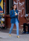Bella Hadid enjoys an ice cream while out for a stroll wearing striped blue blazer and jeans in New York City
