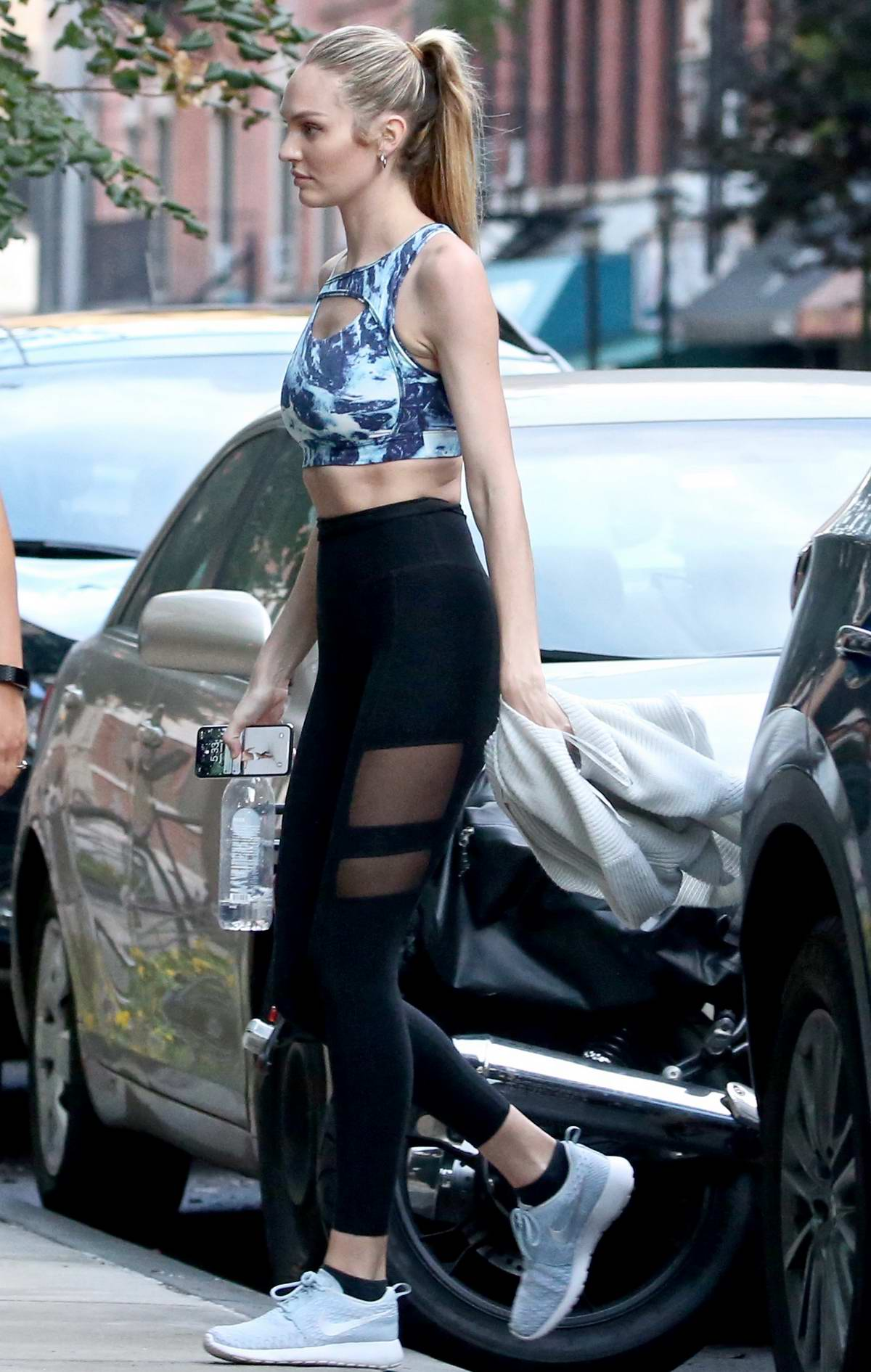 Candice Swanepoel wears a patterned blue crop top, black leggings with Nike trainers as she heads to the gym in New York City