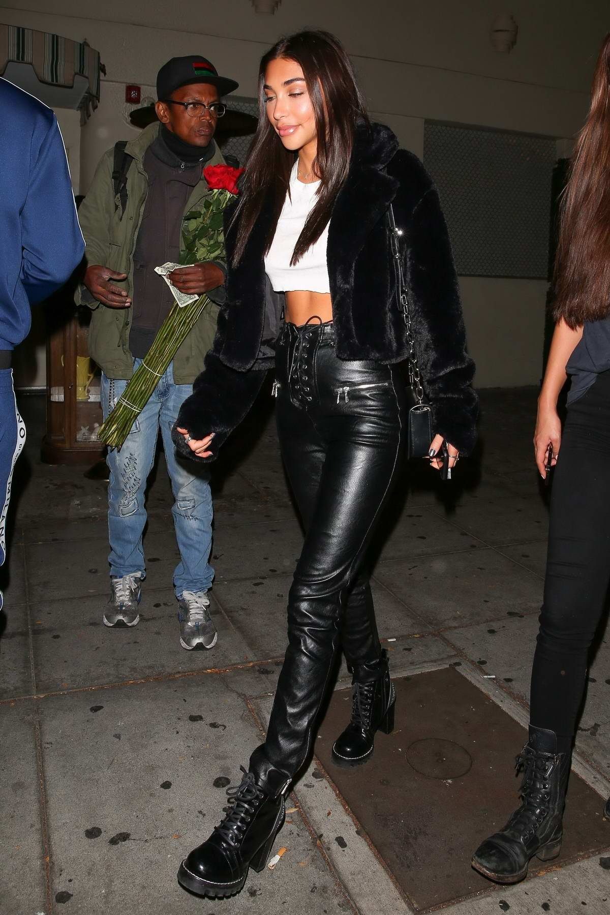 Chantel Jeffries wears a black furry jacket over a white cropped top and black leather pants during a night out at Delilah's in West Hollywood, Los Angeles