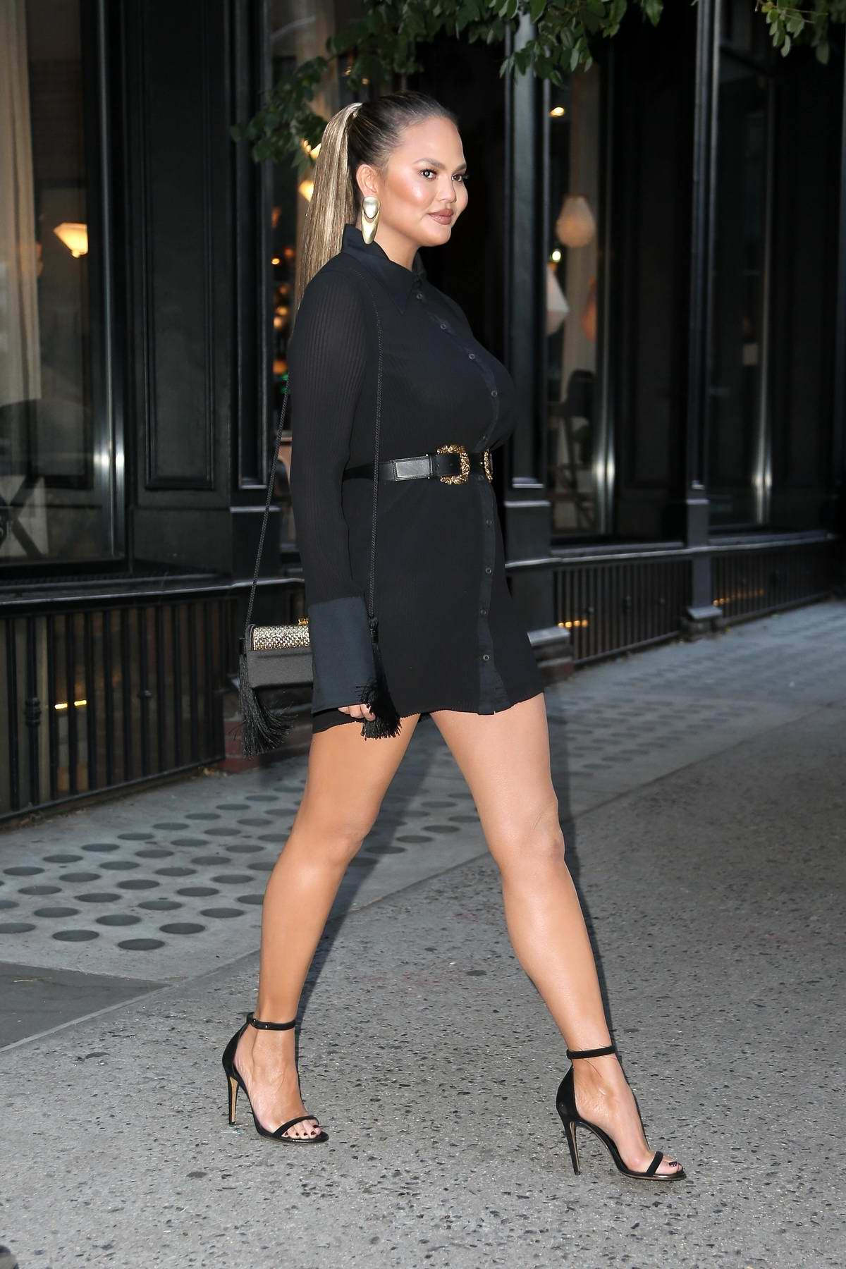 Chrissy Teigen looks stylish in a short black dress as she attends a Store Opening in New York City