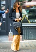 Chrissy Teigen seen wearing a black coat and yellow suede pants while out in Little Italy, New York City