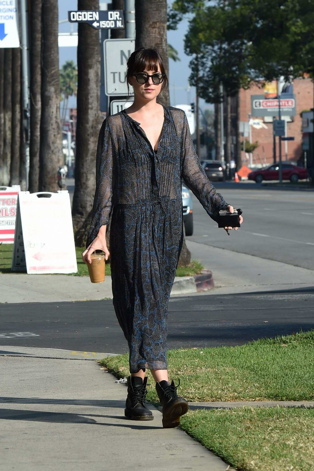 Dakota Johnson seen wearing a sheer black dress as she grabs an iced coffee while running errands in Hollywood, Los Angeles