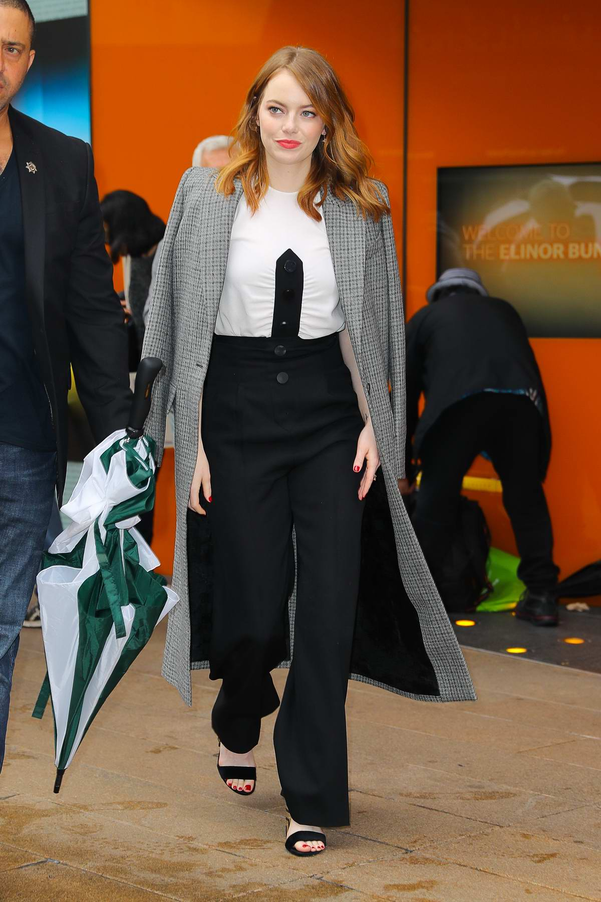 Emma Stone seen wearing a white top with black trousers with a grey coat as she leaves Lincoln Center in New York City