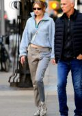 Gigi Hadid rocking a stylish quarter-zip fleece paired with plaided pants and snakeskin boots in New York City