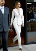 Gigi Hadid steps out in a pristine white pantsuit paired with metallic heels as she leaves her apartment in SoHo, New York City