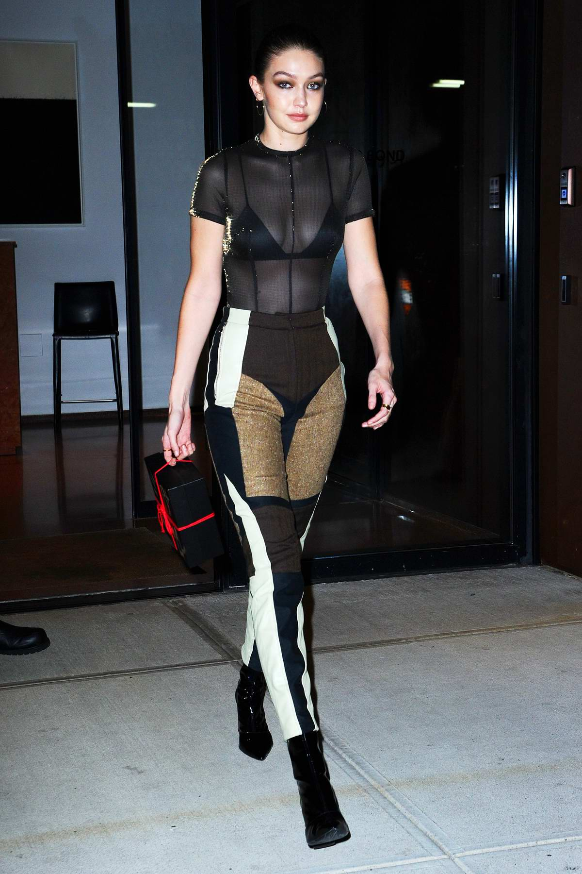 Gigi Hadid wears a black sheer top and patched pants as she heads to Bella Hadid's birthday party in New York City