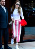 Gigi Hadid wears a white top with a pink and white striped pants as she steps out of her apartment in SoHo, New York City