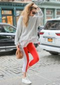 Gigi Hadid wears an off-shoulder white sweater and red leggings while visiting Taylor Swift in New York City