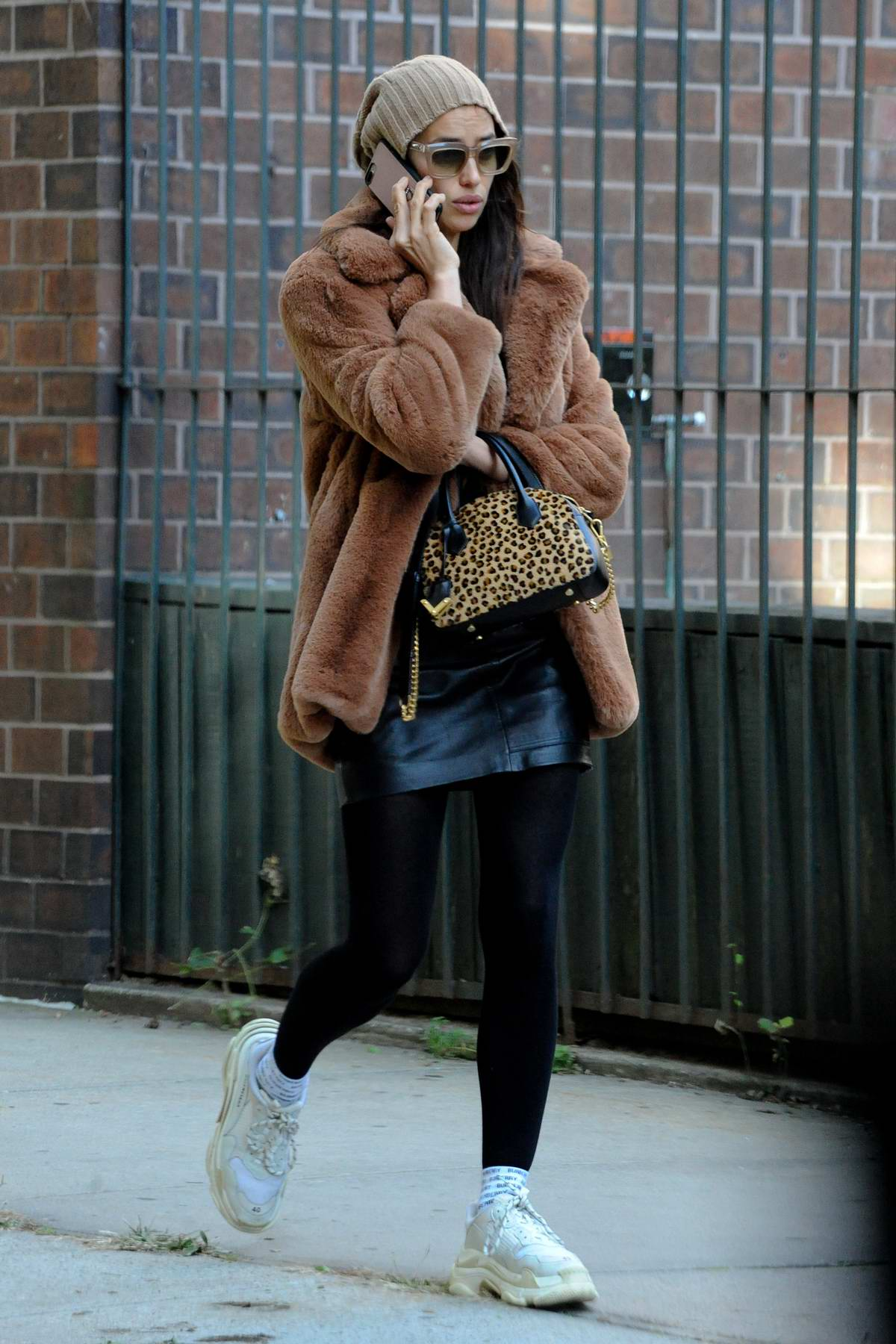 Irina Shayk keeps warm in a brown fur jacket, short leather skirt paired with leggings and a beanie while out talking on her phone in New York City