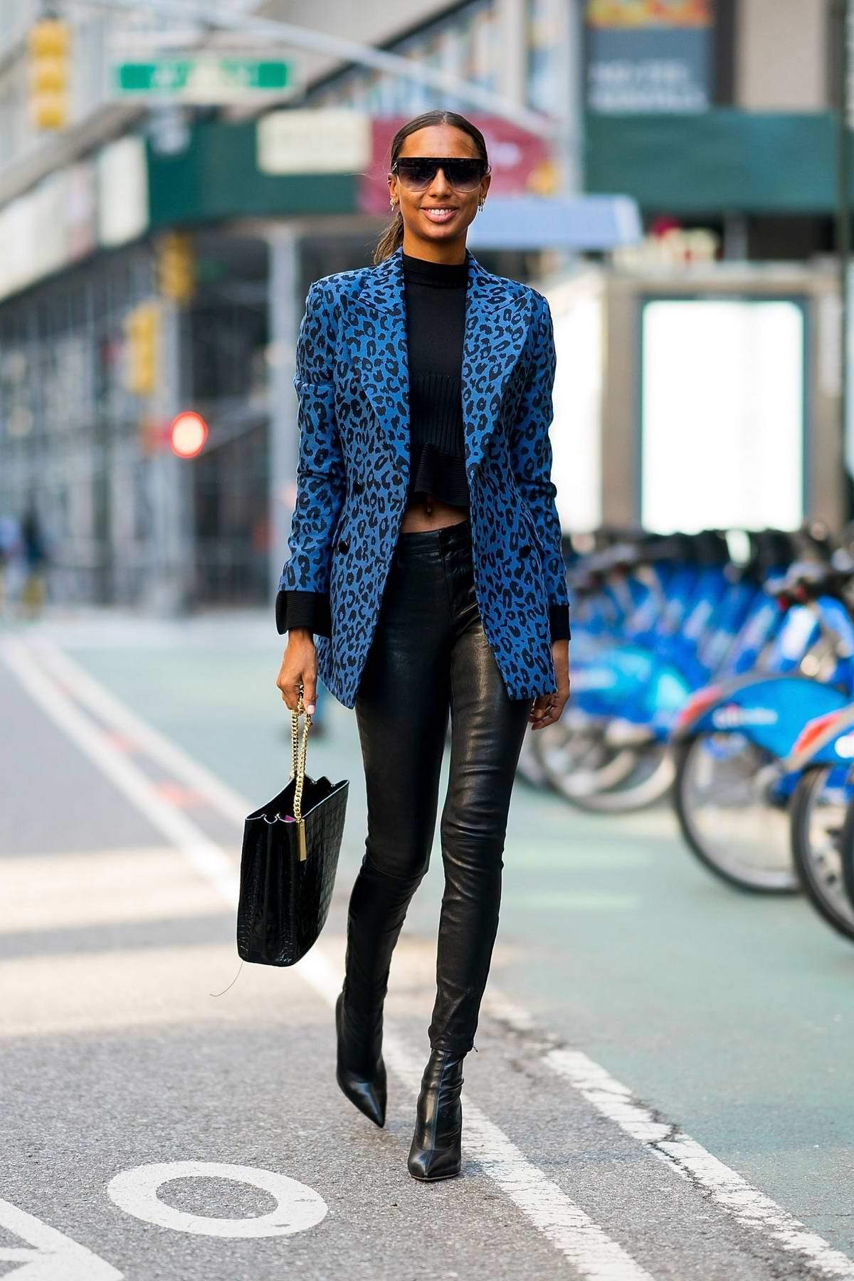 Jasmine Tookes wears an animal print blue jacket with leather pants and boots while arriving for fittings at the Victoria's Secret offices in New York City
