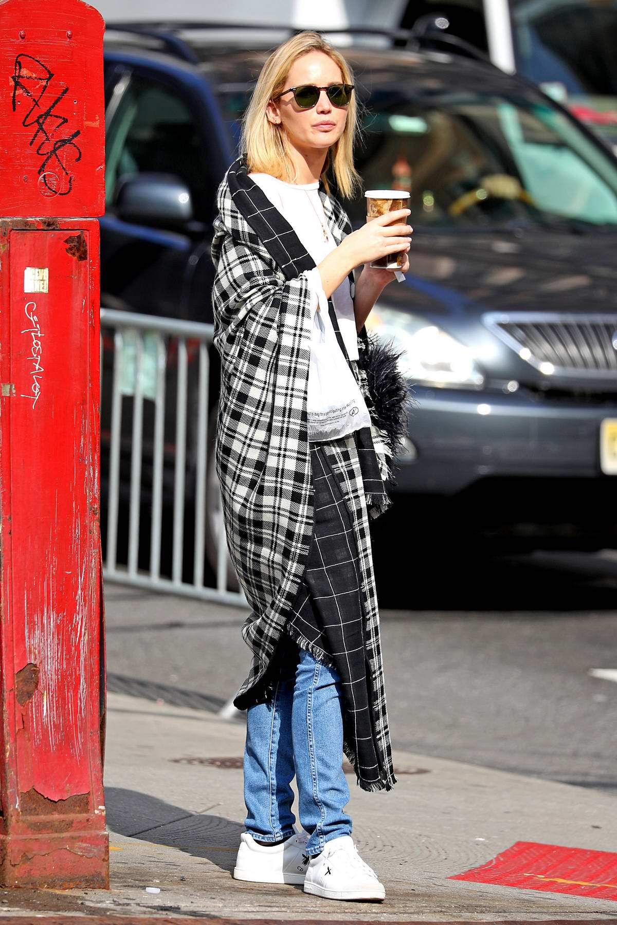 Jennifer Lawrence steps out wearing a plaid cape-scarf while having her coffee in New York City