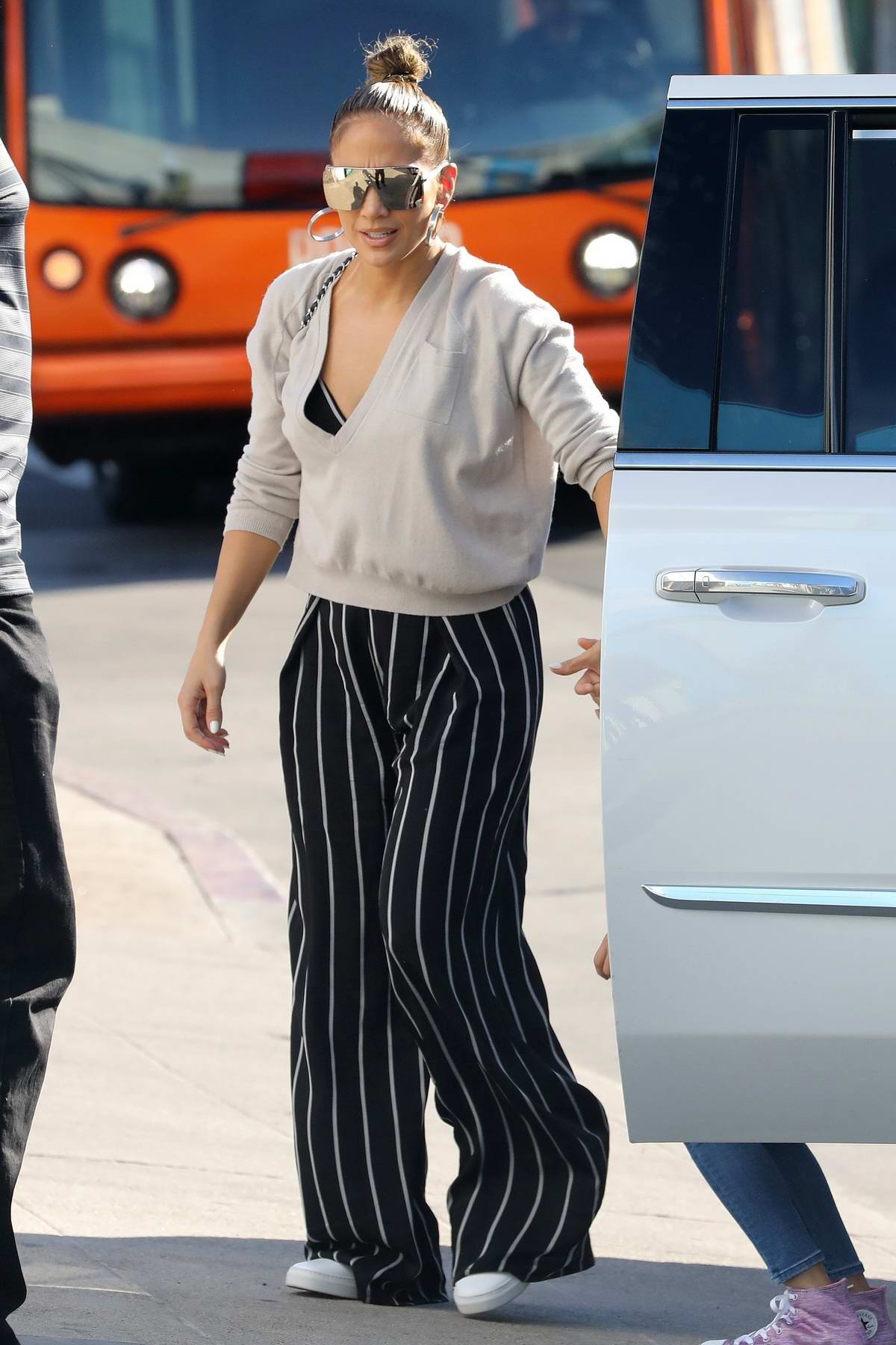 Jennifer Lopez wears a deep neck sweater with a striped jumpsuit as she steps out with her daughter for some shopping in West Hollywood, Los Angeles