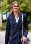 Kaia Gerber is all smiles as she steps out in a blue pantsuit in Paris, France