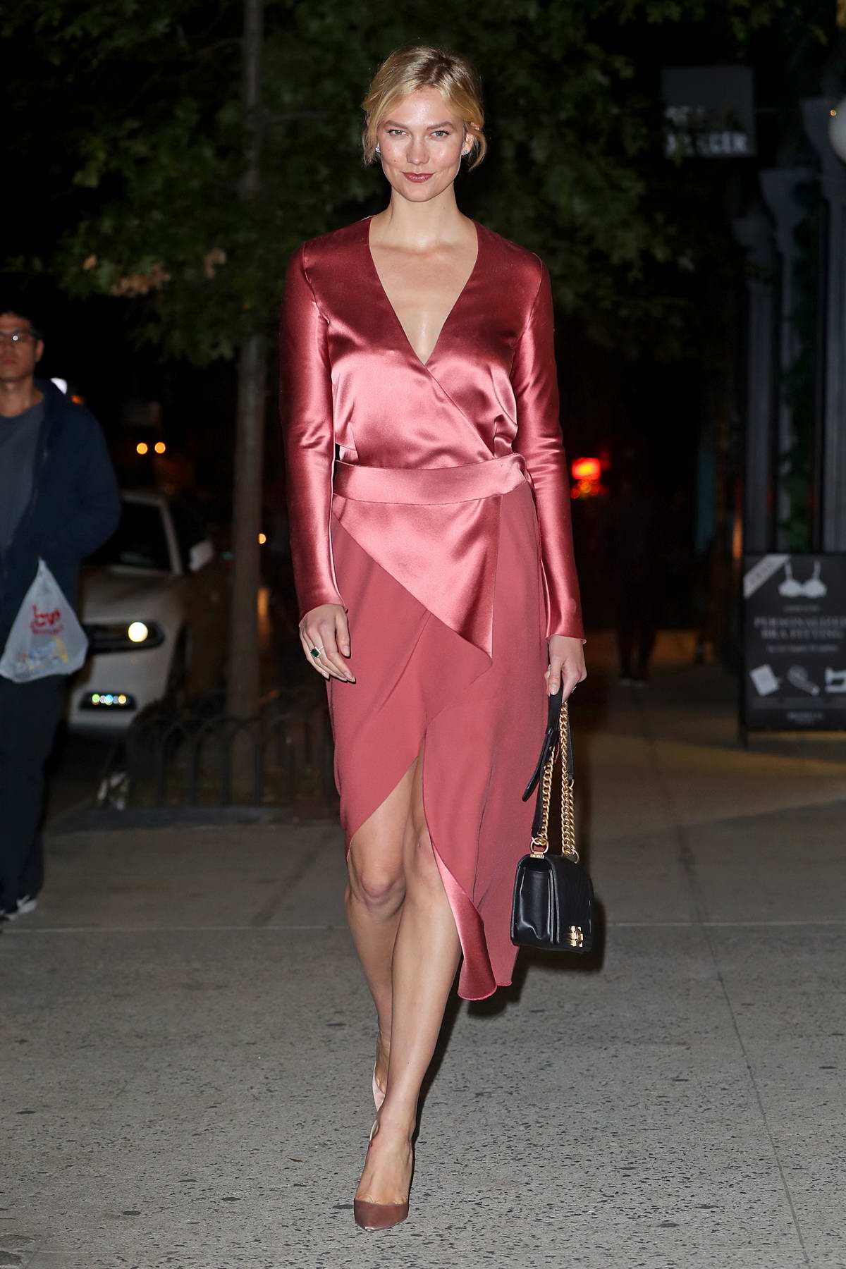 Karlie Kloss heads for a night out in a coral red satin dress in New York City