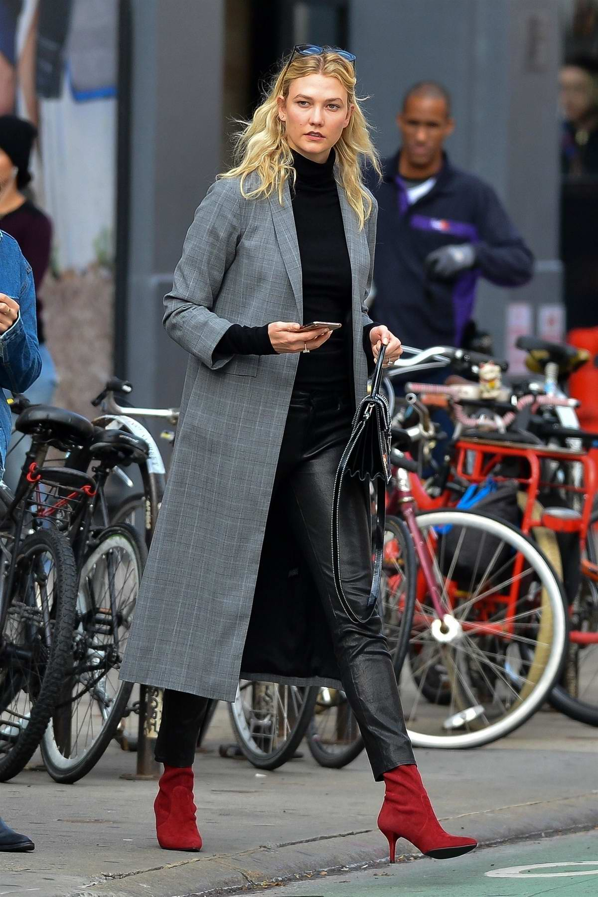 Karlie Kloss looks stylish in a plaid trench coat, black leather pants and red boots as she stepped out for lunch with her family in New York City