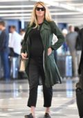 Kate Upton wore a green trench coat over a black outfit as she arrives at LAX airport in Los Angeles