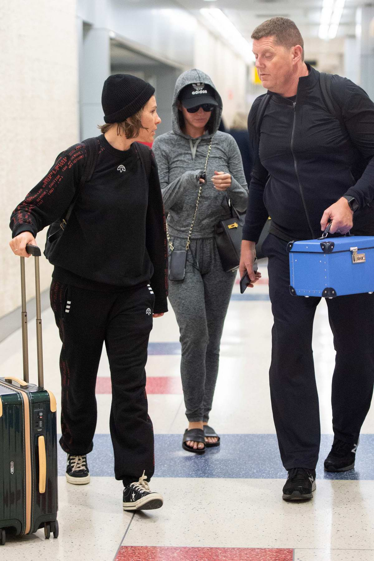 Katy Perry wears an Adidas baseball cap with a grey hoodie, matching sweatpants and sunglasses while arriving at JFK airport in New York City