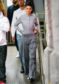 Kendall Jenner steps out in a striped grey shirt paired with loose fit grey trousers while attending a Vogue event at the Milk Studios in New York City
