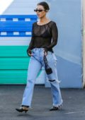 Kourtney Kardashian wears a black sheer top and jeans as she leaves a studio in Los Angeles