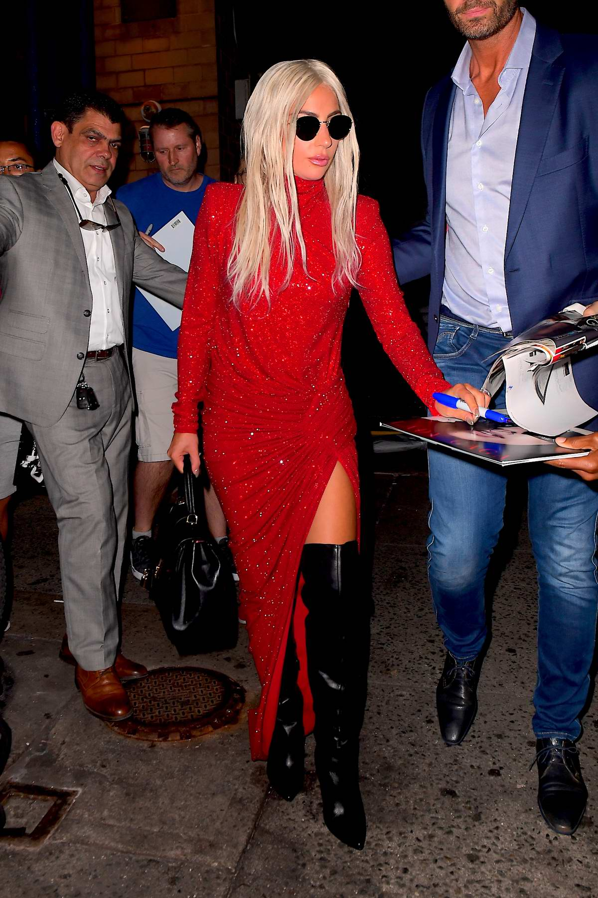 Lady Gaga steps out in a red slit dress with black thigh high boots in New York City