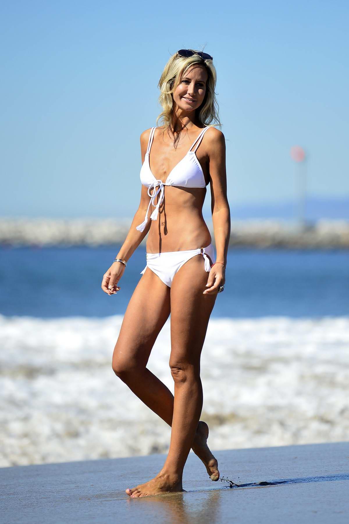 Lady Victoria Harvey wears a white bikini from her own range while on the beach in Malibu, California