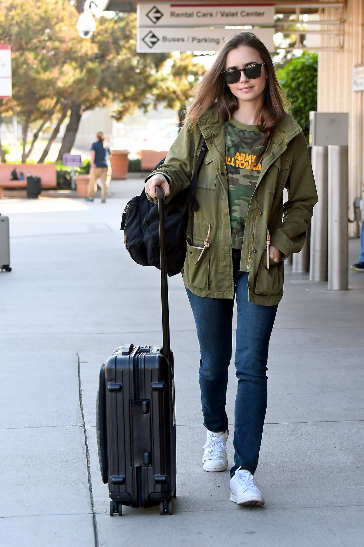 Lily Collins spotted in an olive green jacket and jeans as she arrives at Burbank airport in Los Angeles