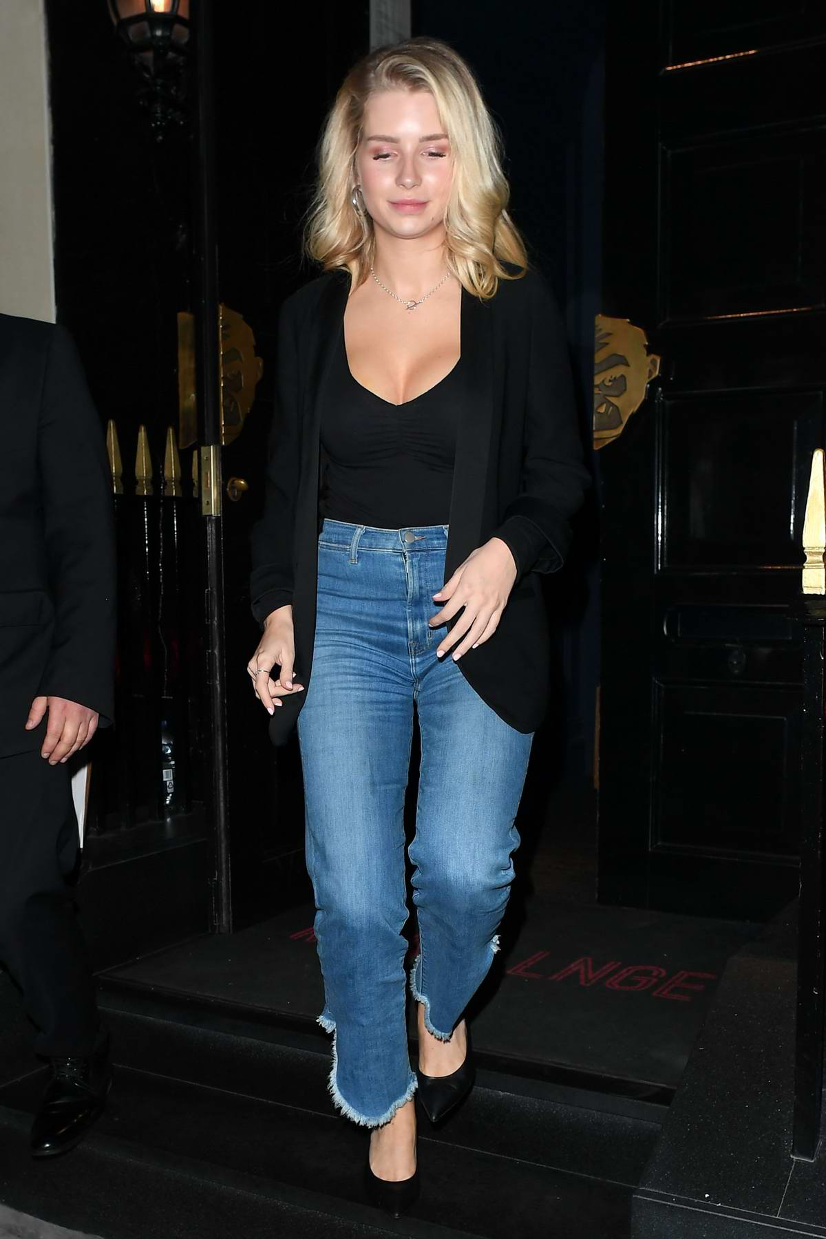 Lottie Moss wears a black blazer with a low-cut top and cropped jean during night out at the Monkey Club in London, UK