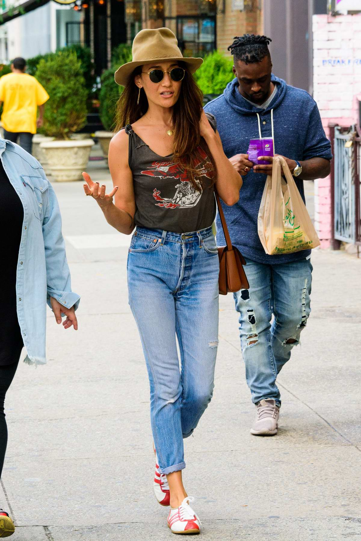Maggie Q seen wearing a hat with Harley Davidson tank top and jeans while out on a stroll with a friend in New York City