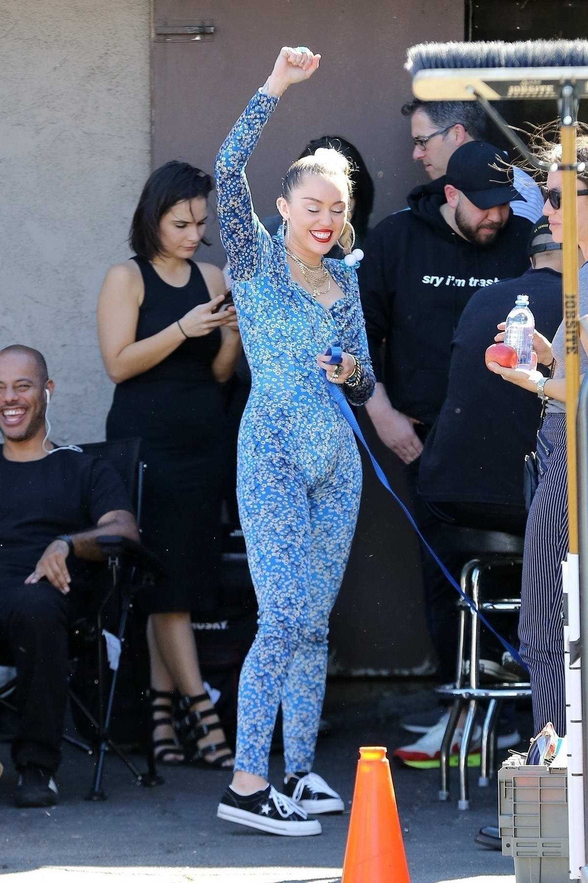 Miley Cyrus seen wearing a blue floral jumpsuit on the set of her new project in Los Angeles